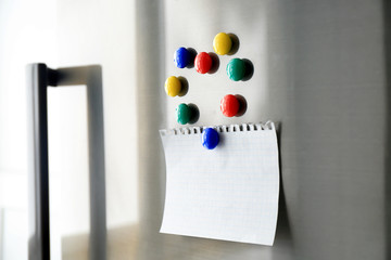 Blank paper sheet with magnets on refrigerator door