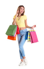 Happy young woman with shopping bags talking on phone against white background