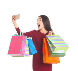Happy young woman with shopping bags taking selfie on white background