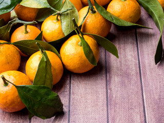 Fresh Mandarin or tangerine with stems and leaves on a brown wooden background copy space