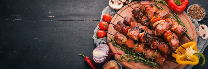 Shish kebab on skewers with onions. On the black wooden table.