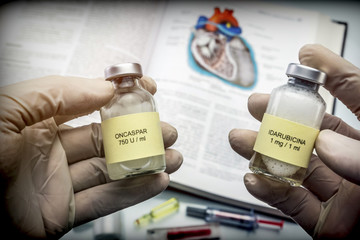 Doctor holds two vials of idarubicina and Oncaspar to inject, medicine used in acute lymphatic leukemia disease