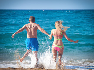 Caucasian man and woman running into the sea water. Back view.