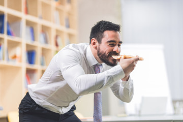A young businessman eats a pizza in his office at a brief break at work.He's careful not to slip off his shirt.