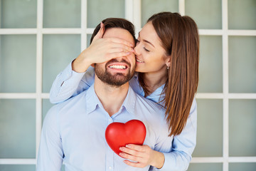 A loving couple with a red heart smiling. Valentine's Day.