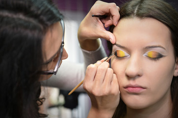 The girl makes up eyes in salon