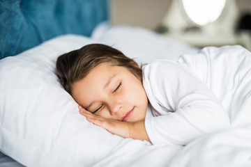 Little girl sleeping in bed peacefully in her bright lit room