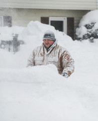 Thomas Berry removes snow from the sidewalk in front of his home after two days of record-breaking snowfall in Erie