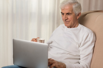 Mature man using laptop during coffee time at home