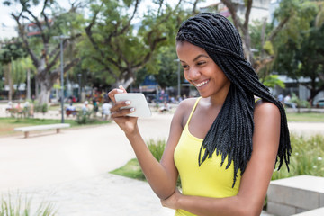 African american young adult woman watching tv with phone