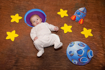 Little baby in costume laying on brown background near stars, rocket, planet