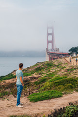 Young man exploring Golden Gate bridge area during cloudy foggy weather.