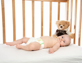 Infant child baby girl toddler lying in bed in diaper with teddy bear