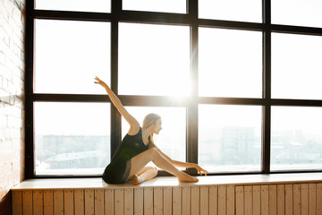 The graceful ballerina in a black pack dances in studio in style the loft with big windows