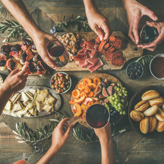 Flat-lay of friends hands eating and drinking together. Top view of people having party, celebrating together at vintage wooden rustic table set with different wine snacks and fingerfoods, square crop