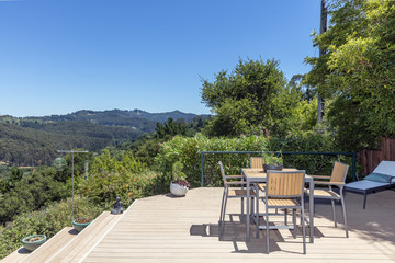 Amazing patio / wooden deck with outdoor furniture and mountain view at daytime.