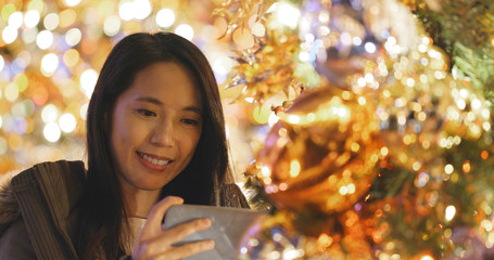 Woman taking photo on mobile phone on Christmas tree decoration at night