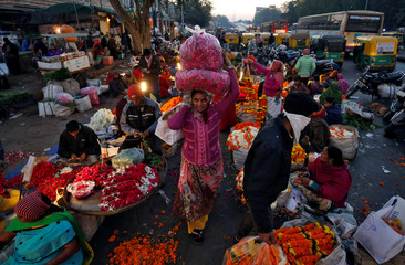 A woman carries flower garlands during early morning at a wholesale flower market in Ahmedabad