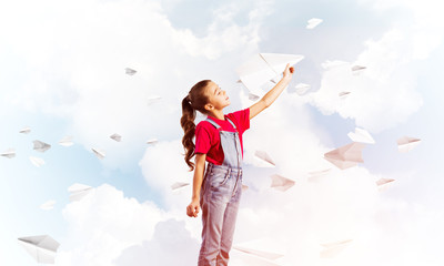 Concept of careless happy childhood with girl throwing paper plane