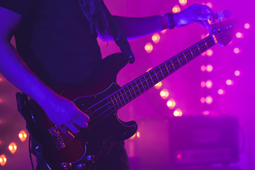 Guitarist tunes electric bass guitar