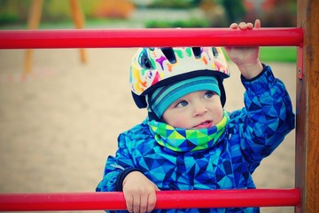 Portrait of toddler climbing a ladder during winter. He has a helmet because of safety.