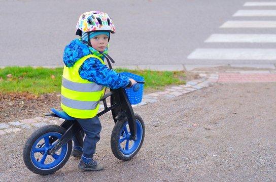 Little boy riding  a push bike in front of pedestrian crossing