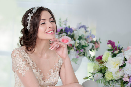 Portrait of beautiful girl in a luxurious wedding dress. Interior decorated with flowers
