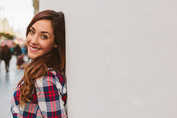 Young Girl Smiling while Leaning Against a White Wall