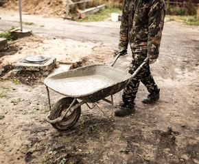 worker pours concrete mortar on a construction site