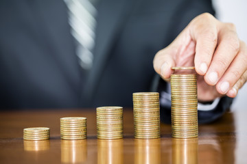 Businessman hand holding one coin on money coin stack arranged as a graph on wooden table, concept of money growth and saving money