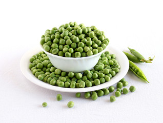 Peas, fresh and organic, in a bowl on a plate with spilled peas, and in the background are pea pods.