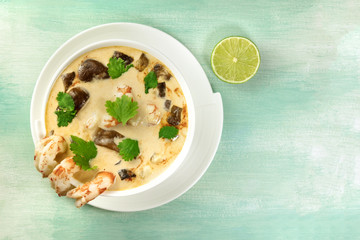 Tom Yam, traditional Thai soup with shrimps and mushrooms, on teal