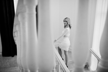 Blonde girl on white dress posed on white stairs of hall.