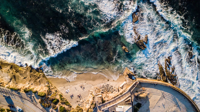 Drone view of waves hitting the rocks and the beach at seashore alongside a park in La Jolla San Diego