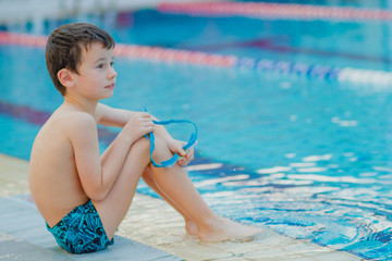 the boy is sitting by the pool