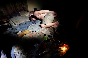 A suspect is pictured inside a drug den during a raid by agents of the Philippine Drugs Enforcement Agency in Tondo, Manila