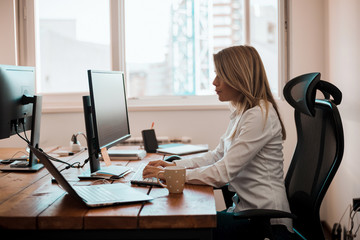 Image of busy woman working on computer in office.