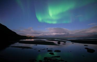 Northern lights background dancing over lake in Abisko national park in Sweden