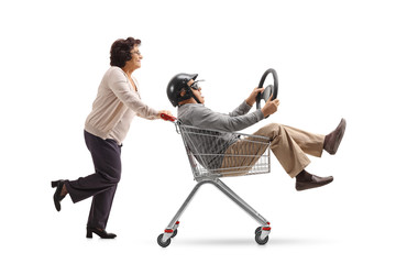 Mature man with a helmet and a steering wheel riding inside a shopping cart being pushed by an elderly woman