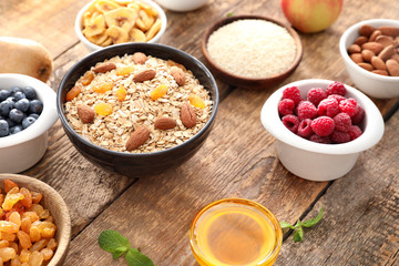 Oatmeal flakes and many different toppings on wooden background