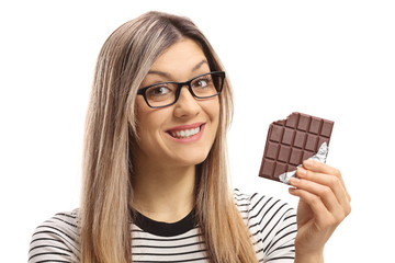 Young woman holding a bitten chocolate bar and smiling