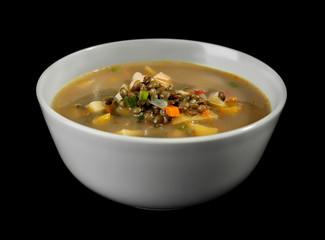Bowl with tasty lentil soup on black background