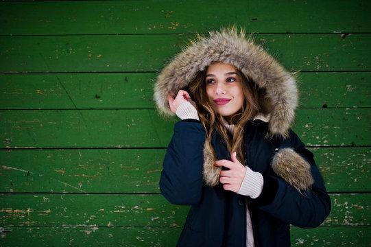 Beautiful brunette girl in winter warm clothing. Model on winter jacket against green wooden background.
