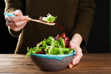 Woman eating fresh salad, closeup