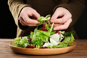 Woman making fresh salad, closeup