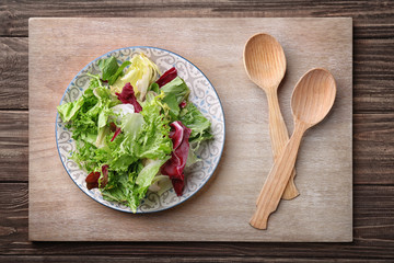Plate with fresh salad on table