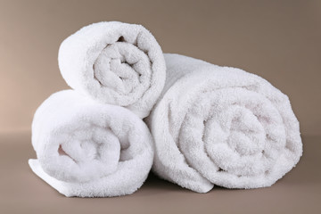Rolled terry towels on color background
