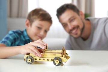 Little boy and father playing with car on table at home