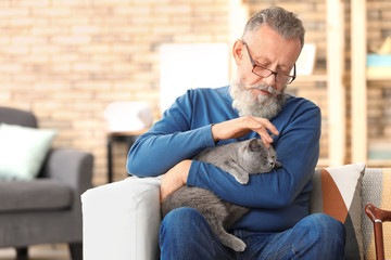 Senior man holding cute cat at home