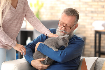 Caregiver giving cute cat to senior man at home